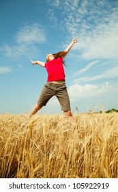 Teen girl jumping at a wheat field in a sunny day