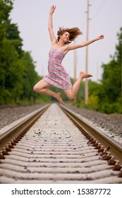 Teen girl jumps on railroad track.