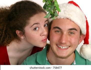 A teen girl kissing a teen boy under the Christmas mistletoe.