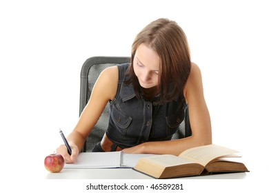 Teen girl learning at the desk with book and note pad, isolated on white