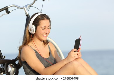 Teen girl listening music from a smart phone sitting with a bike on the beach