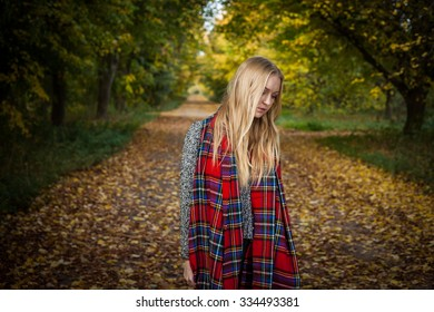 Teen girl with long blonde hair wearing an over size tartan scarf walking along a straight woodland path which stretches into the distance behind