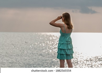 Teen girl with long loose hair in a turquoise dress looking through binoculars on sea and cloudy overcast sky. Back view.