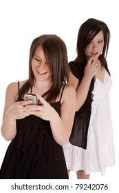 a teen girl looking over a shoulder while her friend is text-ing and enjoying what her friend is text-ing.