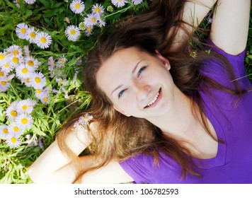 Teen girl lying in grass with flowers