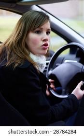 Teen girl mad behind the wheel.