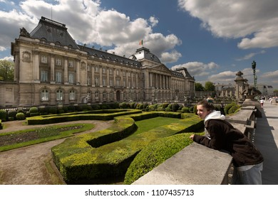 Teen girl next to the royal palace with its gardens in Brussels capital of Belgium. Horizontal take of day.