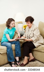 Teen girl and older woman filling out paperwork during an interview. Could be counseling session or job application.  Vertical with copyspace.
