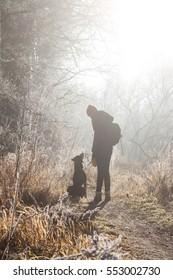 Teen girl on walk with dog at misty morning in forest