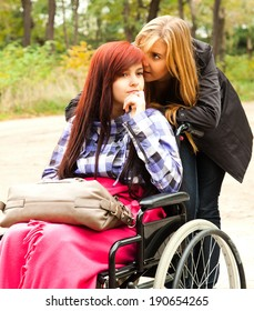 teen girl on the wheelchair with her friend in the park