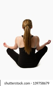 Teen girl on a white background doing yoga from behind with a long pony-tail