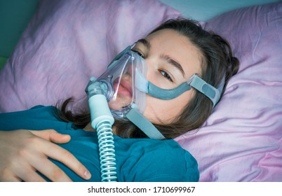 Teen girl in oxygen mask on the bed