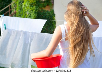 Teen girl with a plastic basin. Drying clean laundry in rope outdoors on sunny day. Young woman is hung up sheets on clothesline