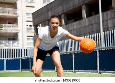 Teen girl playing basketball in an urban court