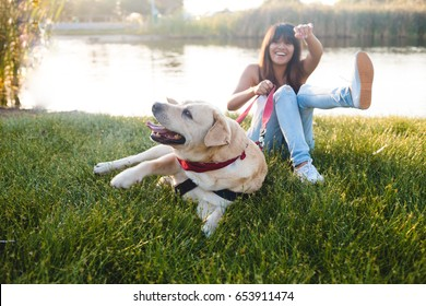 Teen girl playing with dog on grass in park