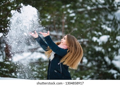 Teen girl playing with snow in an amazing winter.