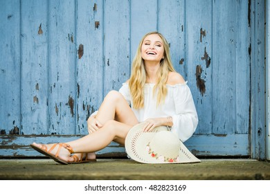 Teen girl poses for a high school senior portrait photo outdoors with wooden blue background