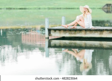 Teen girl poses on dock by a lake for a high school senior portrait photo outdoors