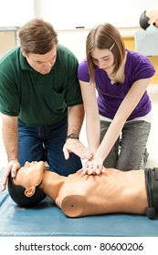 Teen girl practicing CPR on a mannequin, with her teacher's help.