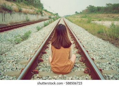 Teen girl with problems sitting on old railway, retro style