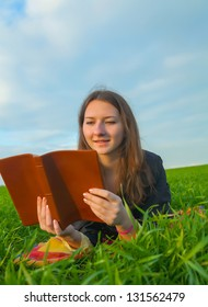 Teen girl reading the Bible laying outdoors at sunset time