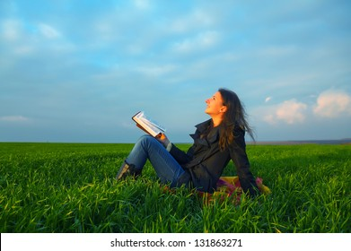 Teen girl reading the Bible sitting outdoors at sunset time
