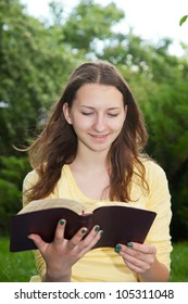 Teen girl reading book outdoors at summer time