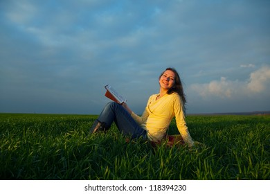 Teen girl reading book outdoors at sunset time