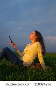 Teen girl reading electronic book sitting outdoors