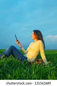 Teen girl reading electronic book outdoors at summer time
