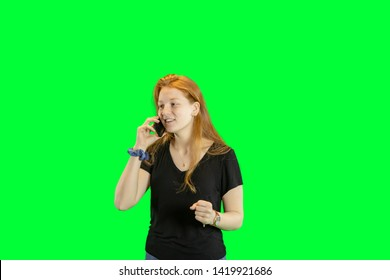 Teen girl with red hair talking on cell phone isolated on green with copy space.