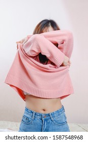 Teen girl  is removing the sweater at home.