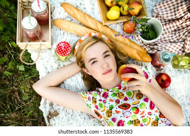 Teen girl resting and eating in park on picnic. Happiness summer weekend concept.