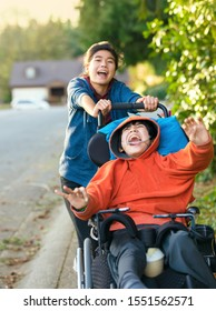Teen girl running and smiling while pushing disabled little boy in wheelchair outdoors