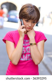 teen girl with sad expression talking to mobile phone