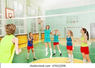 Teen girl serving the ball during volleyball match