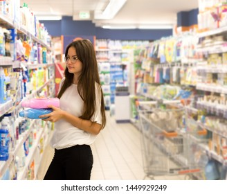 Teen girl shopping in supermarket. Reading product information, choosing daily product