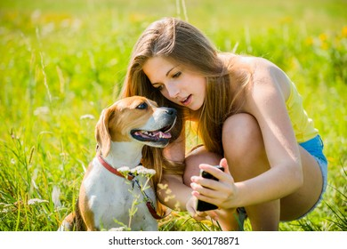 Teen girl showing something to her dog on smart-phone, outdoor in nature