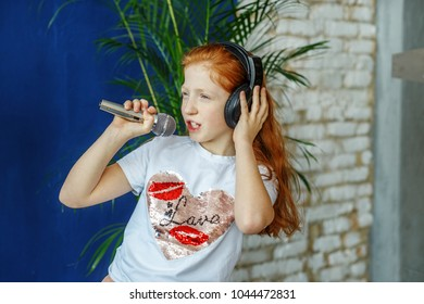 A teen girl sing a song in a microphone. The concept is childhood, lifestyle, music, singing, listening, hobbies.