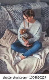 Teen girl sitting on a bed with a toy, the idea of love, comfort, lifestyle hugge lagom