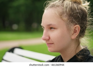 teen girl sitting on bench in park