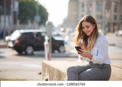 Teen girl sitting on concrete slab and using cell phone
