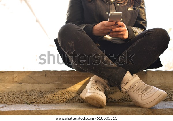 電話を手にしてコンクリートのステップに座る十代の女の子。10代。ヒップスター。通信。外気で。接写。切り抜き写真。