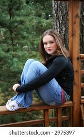 Teen girl sitting on fence