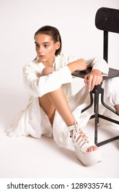 Teen girl sitting on the floor near the chair. Fashionable youth style clothing.