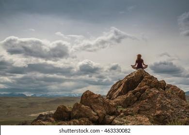 Teen girl sitting on a mountain top