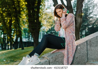 Teen girl sitting on a rock listening to the music with headphones and posing to the camera on summer sunset on the street near park