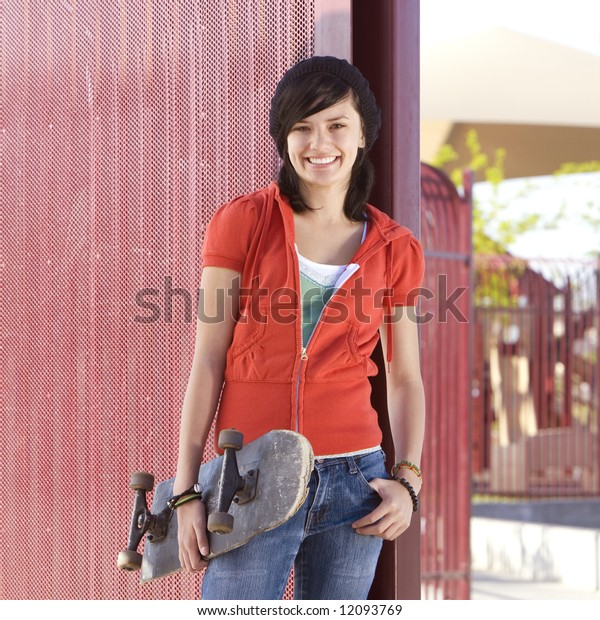 Teen girl with skateboard hangs out at the park