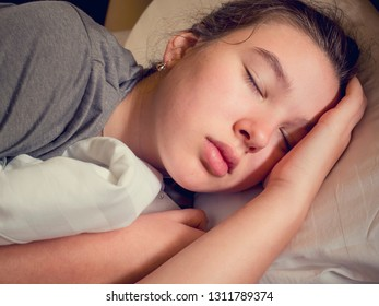 Teen girl sleeping in her bed in the morning at sunrise