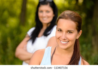 Teen girl smiling with mother in background relaxing outdoors youth